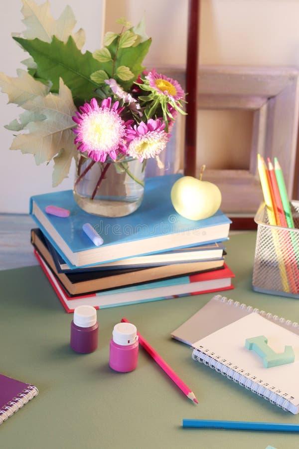 Libros, flores, manzana, efectos de escritorio, marcos y documento coloreado sobre la tabla imagenes de archivo