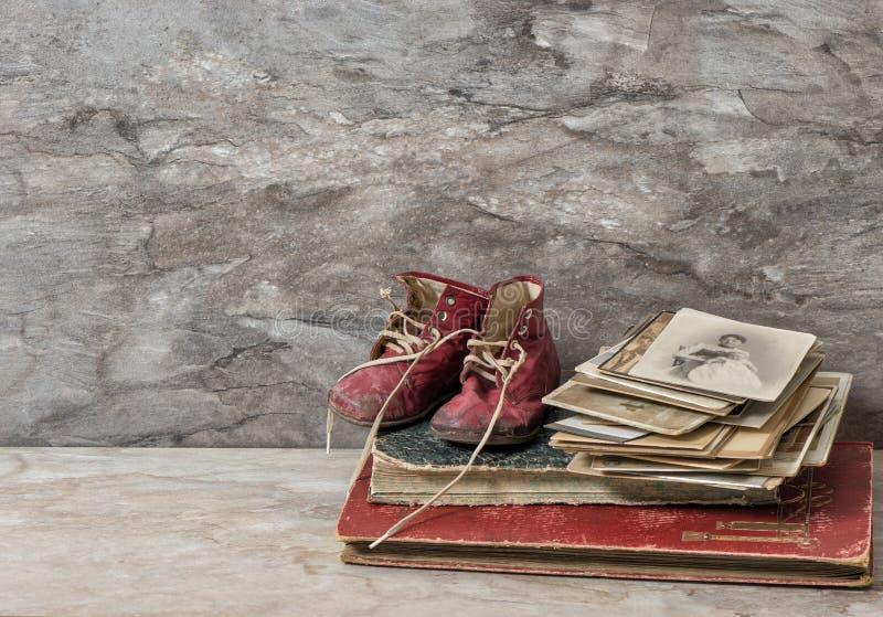 Libros, fotos, y zapatos de bebé antiguos todavía del nostálgico vida foto de archivo
