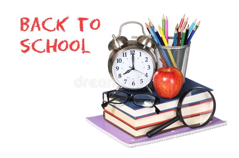 Libros, manzana, despertador y lápices en blanco imagen de archivo