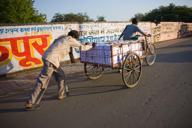 Libros que llevan del hombre indio en el carro del carrito fotografía de archivo libre de regalías