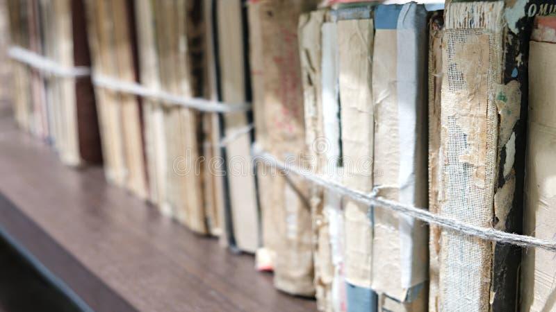Libros viejos del primer atados con una cuerda en estante de madera en la biblioteca o en el archivo fotografía de archivo libre de regalías