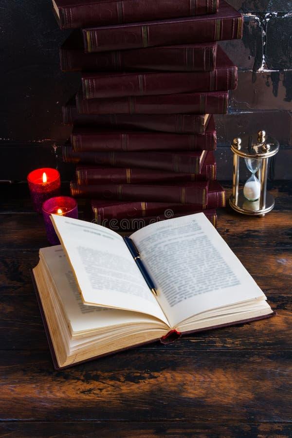 Libros viejos del vintage con la cubierta dura roja que pone como una torre en una tabla de madera oscura y un libro abierto fotos de archivo libres de regalías