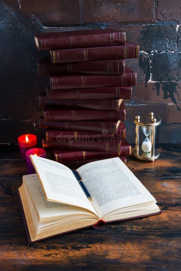 Libros viejos del vintage con la cubierta dura roja que pone como una torre en una tabla de madera oscura y un libro abierto imágenes de archivo libres de regalías