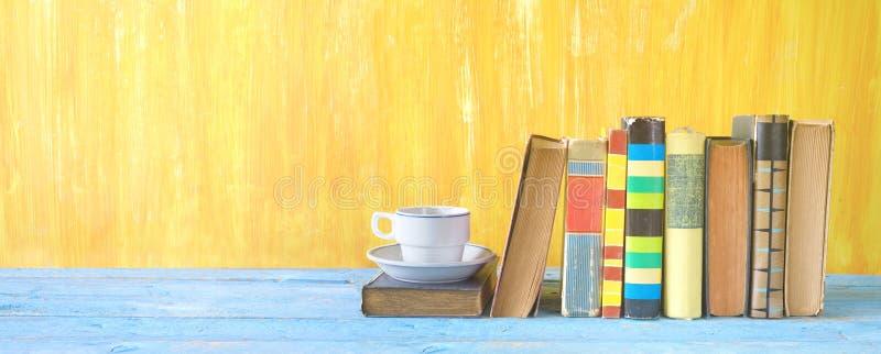 Libros viejos en fila y una taza de café foto de archivo libre de regalías