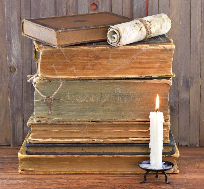 Libros viejos en Web de araña con la vela fotos de archivo libres de regalías