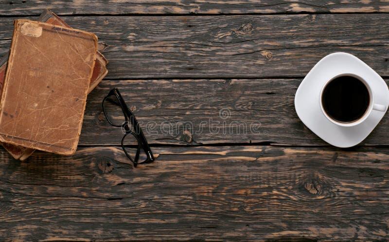 Libros viejos, gafas y taza de café apilados foto de archivo