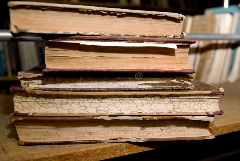 Libros viejos que mienten en un estante en la biblioteca foto de archivo libre de regalías