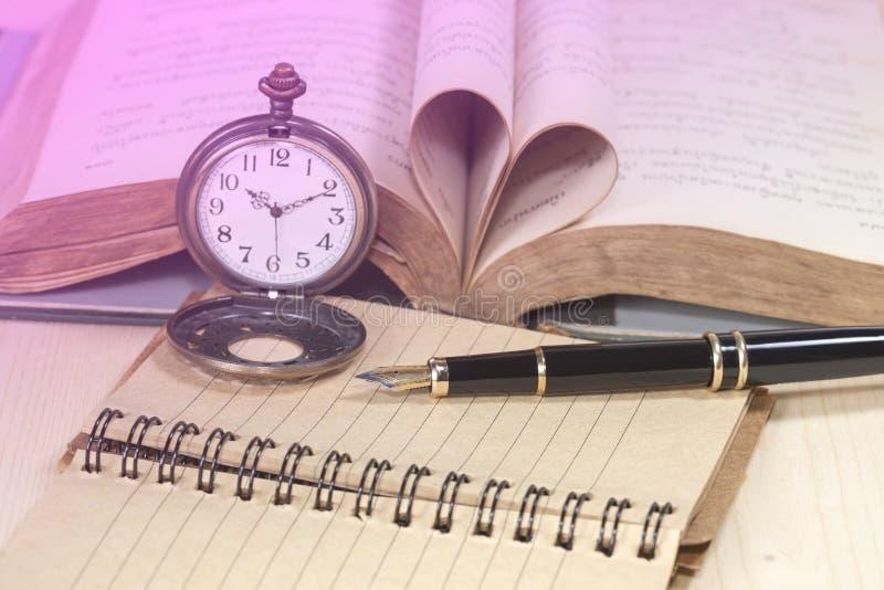 Libros viejos, reloj del bolsillo, papel y pluma imágenes de archivo libres de regalías