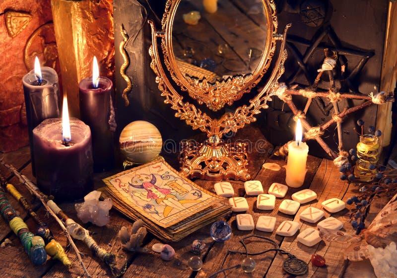 Libros viejos, velas negras, espejo, cartas de tarot y runas en la tabla de la bruja imagen de archivo