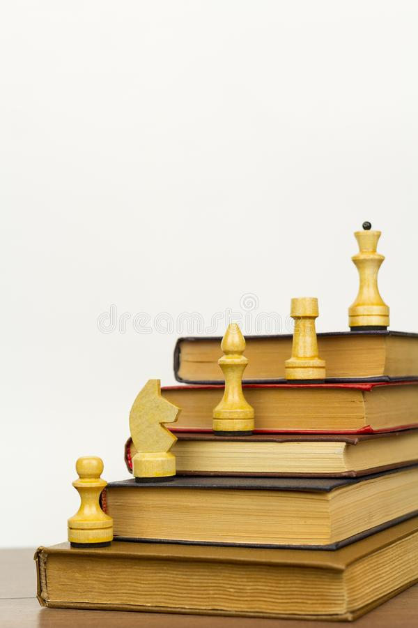 Libros viejos y pedazos de ajedrez en una superficie de madera imagen de archivo libre de regalías