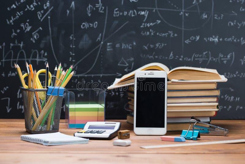 Libros y efectos de escritorio de escuela en una madera y un backgroun de la pizarra fotografía de archivo libre de regalías