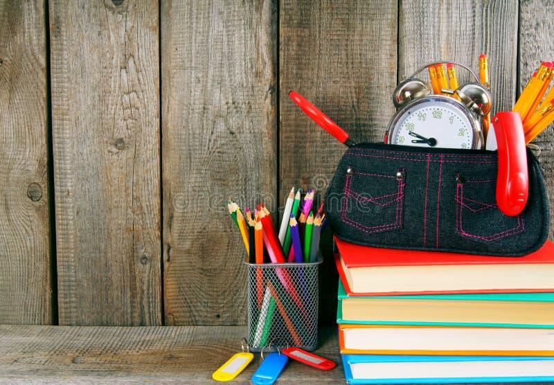 Libros y herramientas de la escuela en un estante de madera fotos de archivo