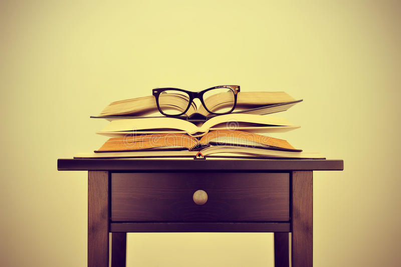 Libros y lentes en un escritorio, con un efecto retro fotos de archivo libres de regalías