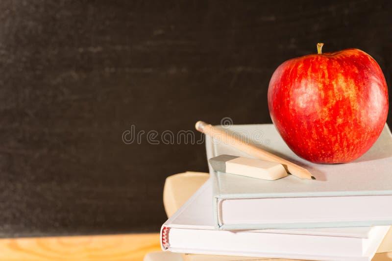 Libros y manzana académicos tradicionales de escuela del estudio fotografía de archivo libre de regalías