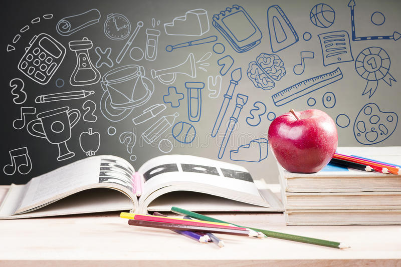 Libros y manzana de escuela contra la pizarra imagen de archivo
