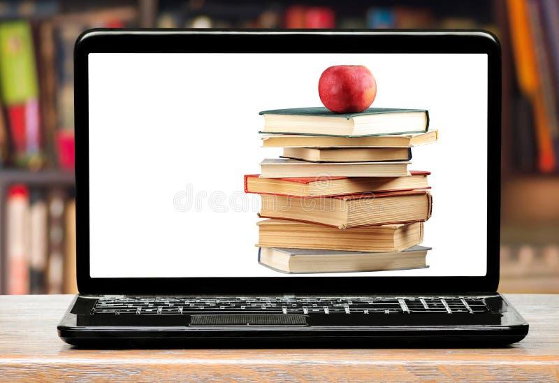 Libros y manzana en la pantalla del ordenador portátil imagen de archivo