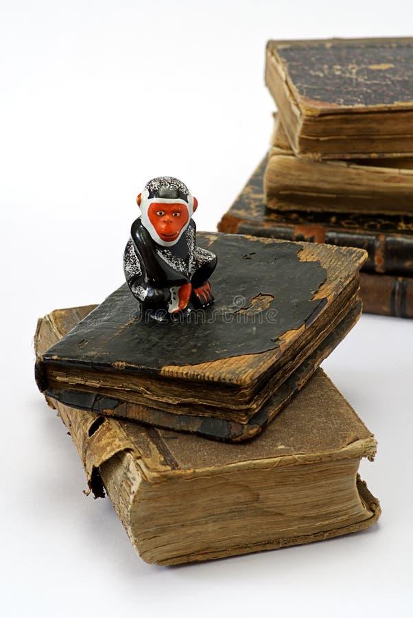Libros y mono religiosos viejos foto de archivo