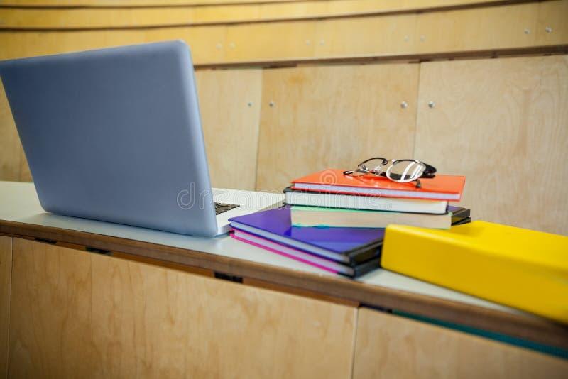 Libros y ordenador portátil de los estudiantes en un auditorio imagen de archivo libre de regalías