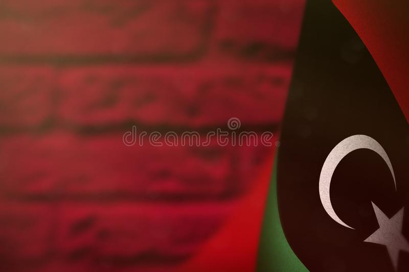Libya flag for honour of veterans day or memorial day. Glory to the Libya heroes of war concept on red blurred painted brick wall. Libya hanging flag for honour stock photo