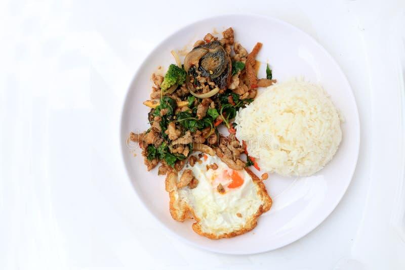 Licencia sofrita de la albahaca con cerdo picadito, pollo, huevo y zanahoria preservada frita, maíz amarillo, bróculi con arroz y fotografía de archivo