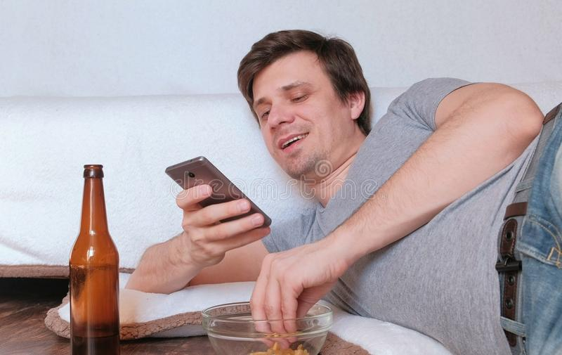 Licenciado considerável do homem novo que come microplaquetas e que bebe a cerveja e que consulta seu telefone celular fotografia de stock