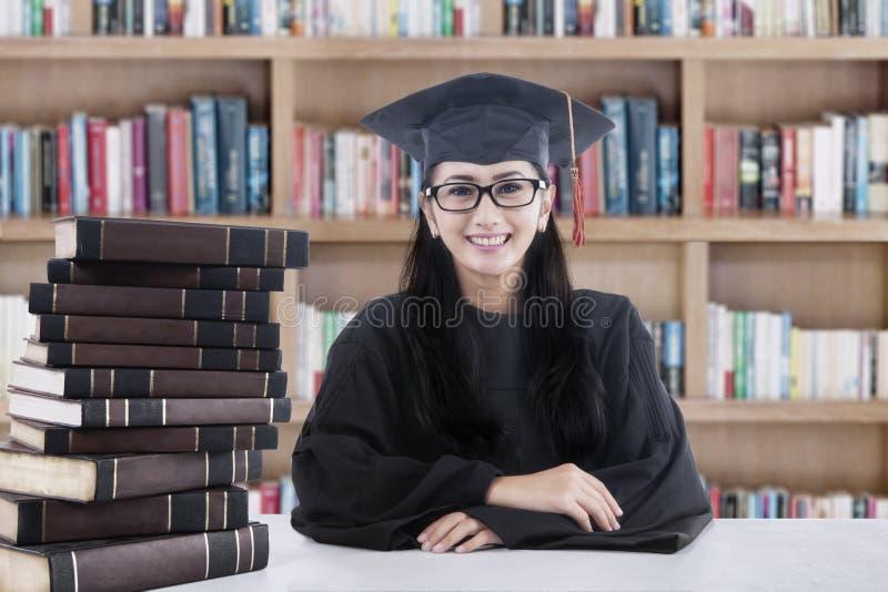 Licenciado e livros fêmeas na biblioteca foto de stock