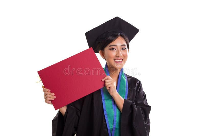 Licenciado fêmea novo que mostra seu close up do certificado da graduação imagem de stock