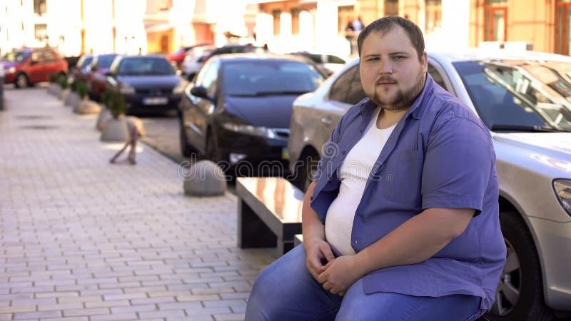 Licenciado gordo triste que senta-se no banco apenas, sentindo só, não tendo nenhum amigo imagem de stock royalty free
