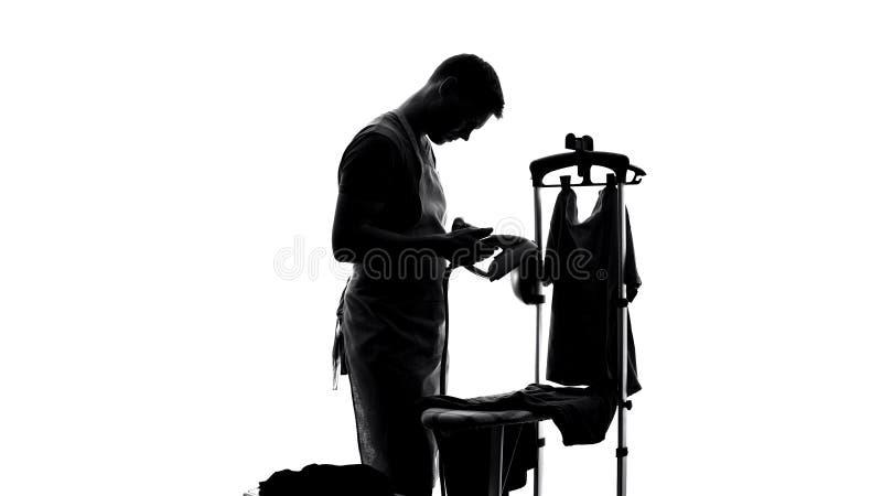 Licenciado novo que tenta passar a roupa, rotina de tarefas domésticas, ajuda do marido fotografia de stock
