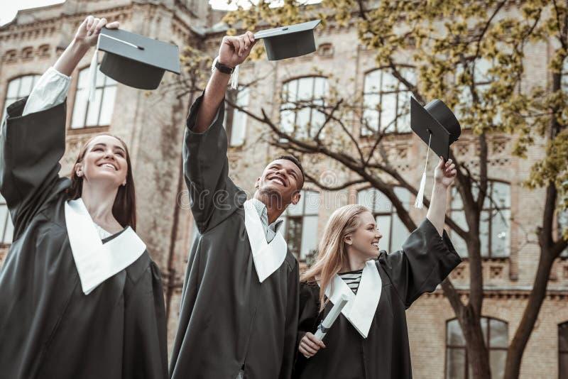 Licenciados deleitados positivos que aumentam seus chapéus da graduação imagens de stock