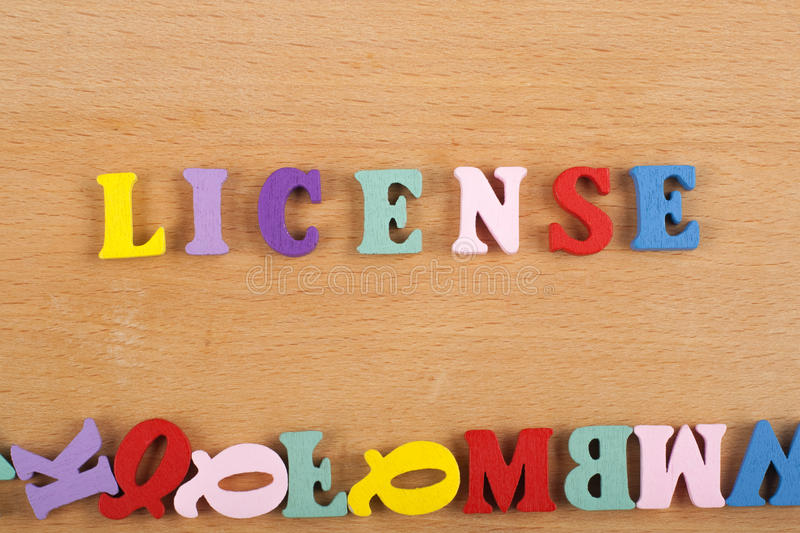 LICENSE word on wooden background composed from colorful abc alphabet block wooden letters, copy space for ad text royalty free stock photography