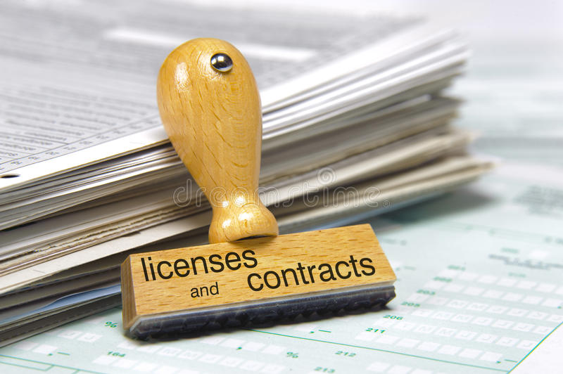 Licenses and contracts. Printed on rubber stamp over documents stock photos