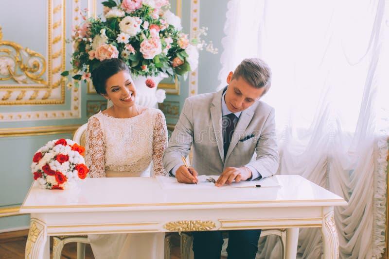 Licenza di matrimonio di firma dello sposo e della sposa immagine stock libera da diritti