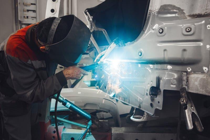 Lichaam van de metaal het werkende auto met de machine van het kooldioxidelassen Reparatie van voertuig in dienst na het ongeval  stock fotografie