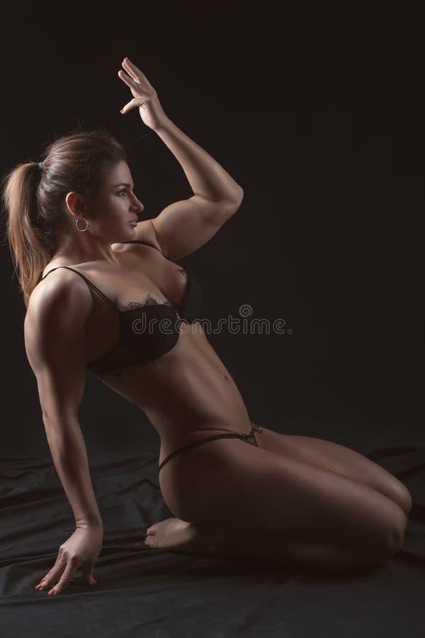 Lichaamssporten een aantrekkelijke vrouw op een zwarte achtergrond royalty-vrije stock foto's