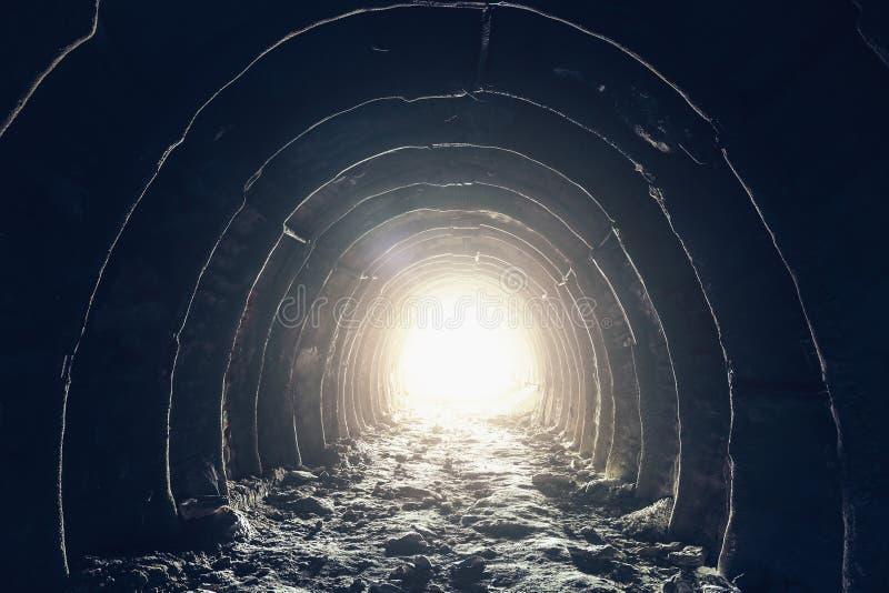 Licht aan het eind van donkere industriële tunnel, verlaten ondergrondse hol of mijn, uitgang of vlucht aan vrijheids licht conce stock foto