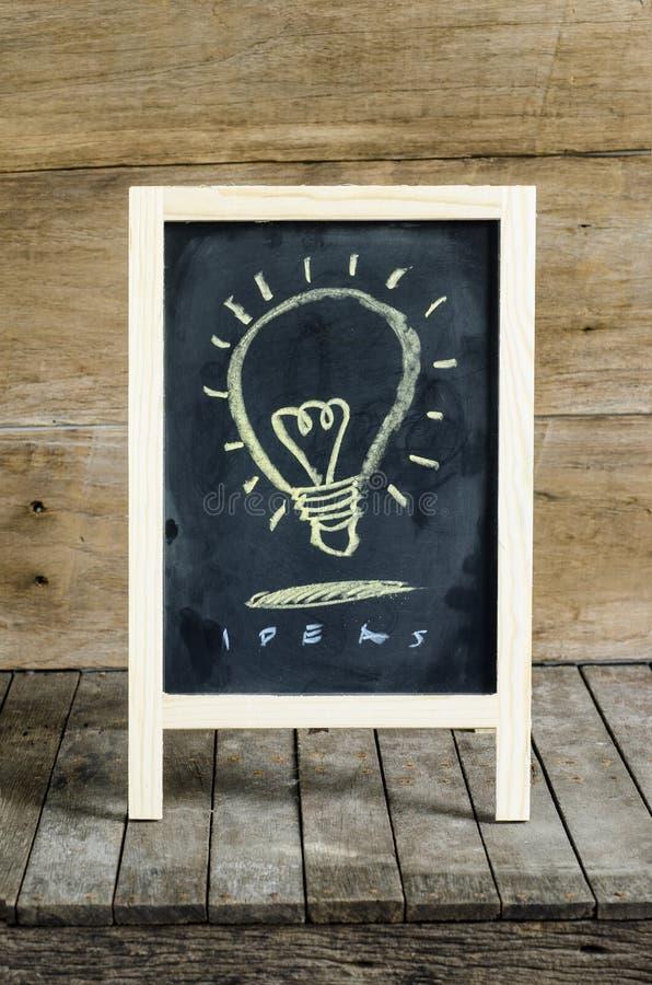 Licht Blub-Bord die op houten achtergrond trekken royalty-vrije stock afbeeldingen