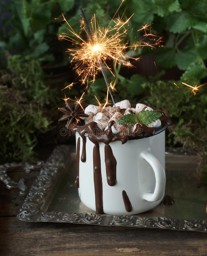 Licht Christmassy Bengal in einer Schale heißer Schokolade mit Eibischen, Nüssen und Zimt auf einem Weinlesesilbertablett, selekt stockbilder