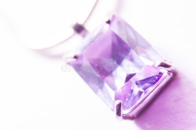 Licht, das durch einen violetten Anhänger glänzt stockbilder