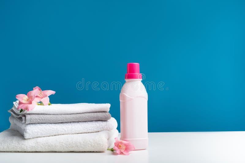 Licht gekleurde handdoekenstapel door fles van plastificeermiddel stock afbeelding