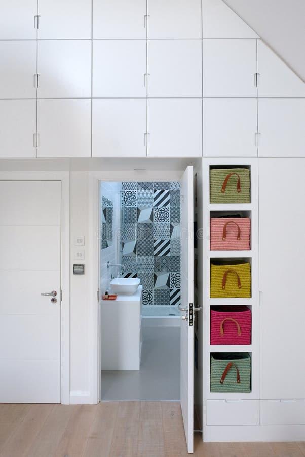 Licht-gevuld slaapkamerbinnenland die ensuite badkamers met zwart-wit tegels onderzoeken royalty-vrije stock fotografie