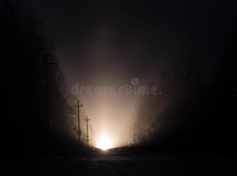 Licht in het eind van een weg op nacht royalty-vrije stock afbeelding
