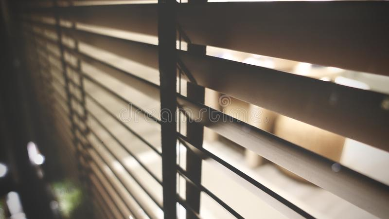 Licht innerhalb des Badezimmers und hölzerne Jalousien, Sonnenschein und Schatten auf Jalousie- und Granitfliesenwand stockbilder