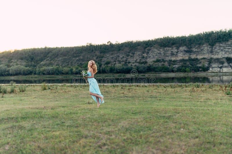 Licht krullend meisje in een blauwe kleding, photosession in de lente op de aard royalty-vrije stock afbeelding