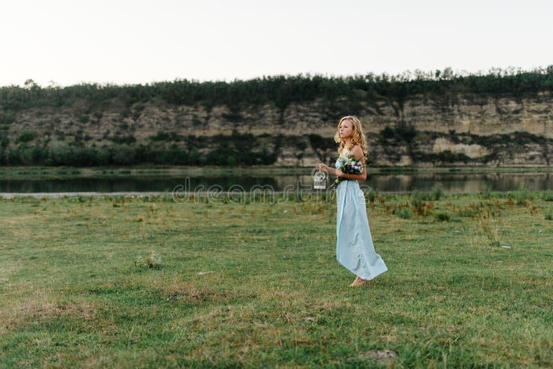 Licht krullend meisje in een blauwe kleding, photosession in de lente op de aard stock foto's