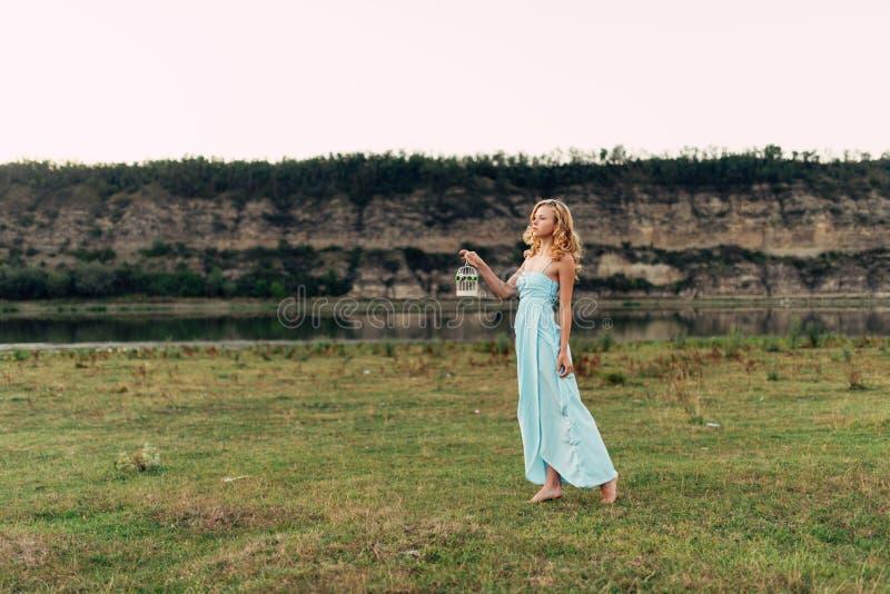 Licht krullend meisje in een blauwe kleding, photosession in de lente op de aard stock afbeeldingen