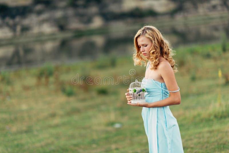 Licht krullend meisje in een blauwe kleding, photosession in de lente op de aard royalty-vrije stock foto's