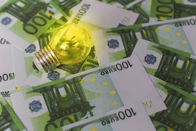 Licht op de achtergrond van Euro geld, dure elektriciteit stock fotografie