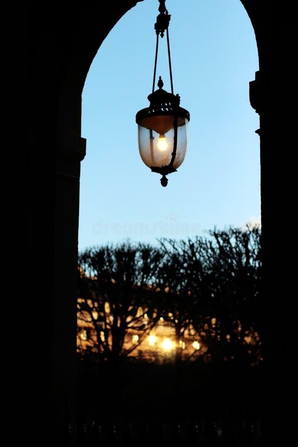 Licht van de de arcadelantaarnpaal van Palais het koninklijke tuinen bij zonsondergang in Parijs stock foto