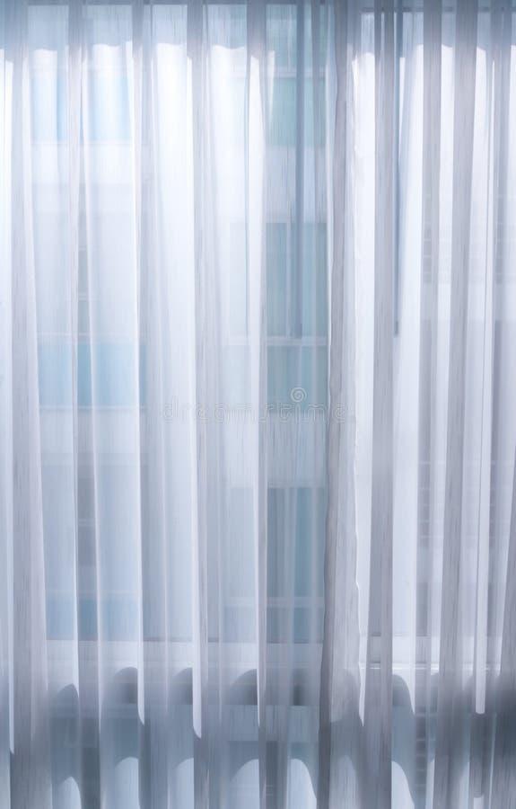 Licht van de rug van een dun wit gordijn stock foto